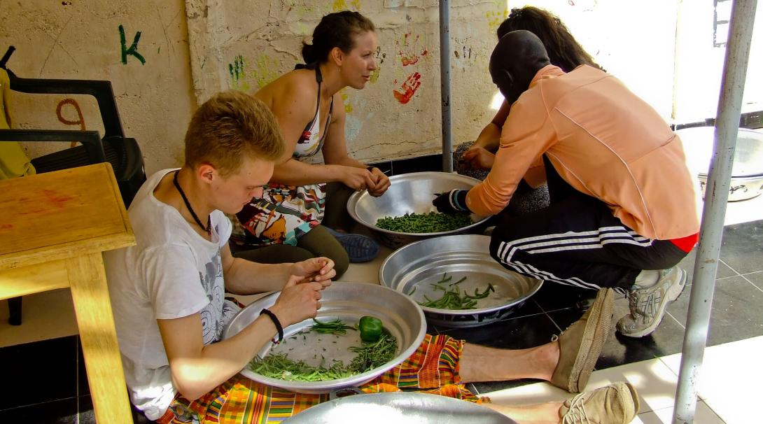 Projects Abroad volunteers peeling greens and getting to know the locals on their French Language Project in Senegal